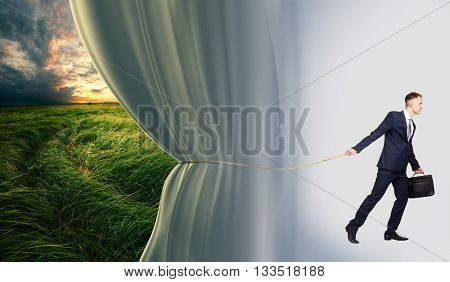 Young businessman with briefcase removes blue curtain to represent the beautiful meadow on the background