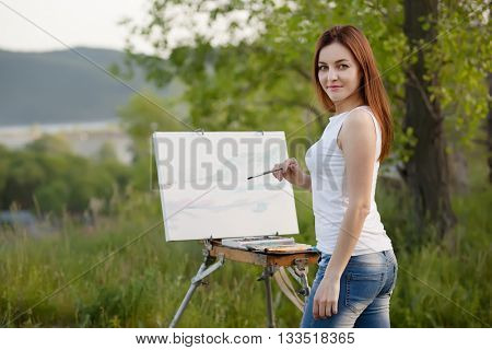 Young lovely caucasian woman painting outdoors
