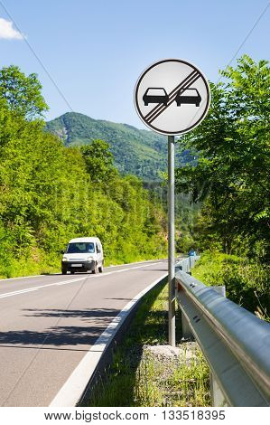 End of overtaking prohibition road traffic sign on a signpost at the side of a mountainous road with an approaching white car