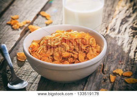 Bowl of corn flakes and glass of milk, on wooden surface.