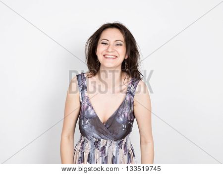 beautiful young brunette woman in a colorful dress posing and expresses different emotions. woman's hands shows various signs, disco. close-up portret.