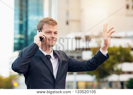 Businessman talking on the phone hailing a taxi while standing in the city