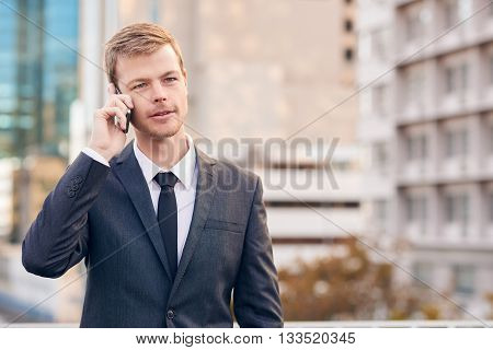 Young businessman talking on a cellphone while standing in the city
