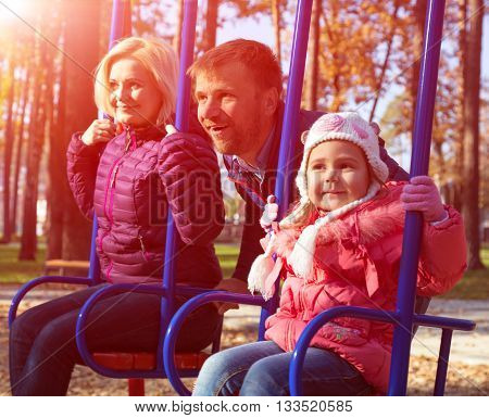 Young European Family of Three People Man Woman Baby Girl Riding on Seesaw in Autumnal Park Outdoor Day