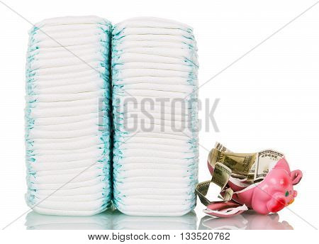 Stacks of diapers, broken piggy bank and money isolated on white background.