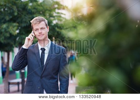 Young businessman talking on a cellphone while walking in the city