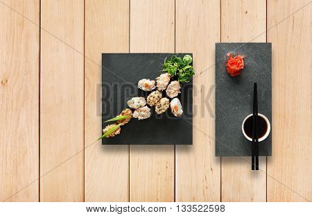 Japanese food restaurant, sushi gunkan plate or platter set. Set for two with chopsticks, ginger, soy, wasabi. Sushi at wooden planks background. Top view, flat lay, copyspace