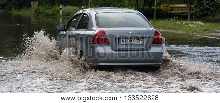 CHERKASSY, UKRAINE- JUNE 5, 2016: car driving on a flooded road during a flood caused by heavy rain, in Cherkassy.