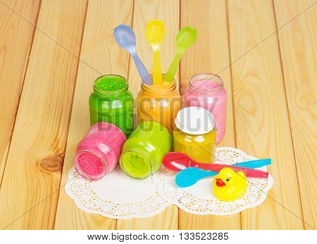 Jars of various puree, colored plastic spoons and rubber duck on a background of light wood.