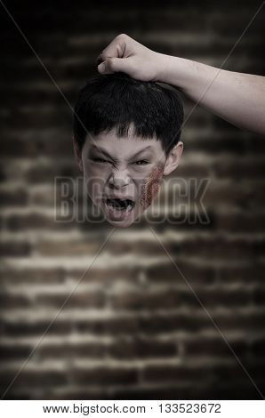 Hand holding little zombie head in the dark