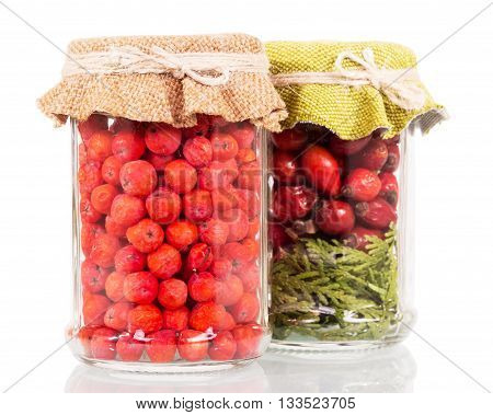 Jars with rowan berries and rose hips isolated on a white background.