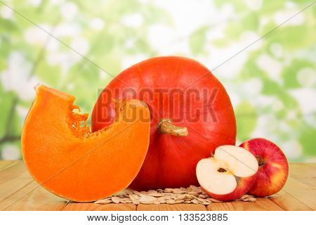 Ripe pumpkin seeds and apples on abstract green background.