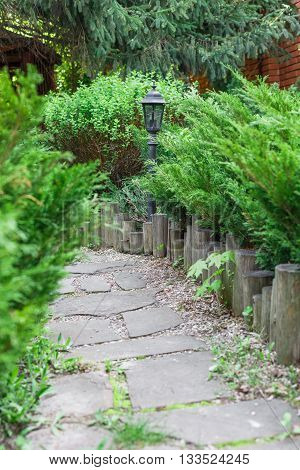 Beautiful landscape design, garden path with park light, wooden fence, stone tile, evergreen bushes and shrubs in sunlight. Modern landscaping. Summer garden or park design.