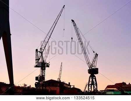 Harbor crane in the sunset. High contrast freight crane in a container harbor. Hamburg Harbor in the dusk.