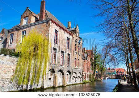 Bruges, Belgium - April 10, 2016: Scenic cityscape with medieval houses and canal in Bruges, Belgium