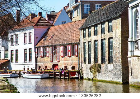 Bruges, Belgium - April 10, 2016: Scenic cityscape with medieval houses, cruise boat station with tourists and canal in Bruges, Belgium