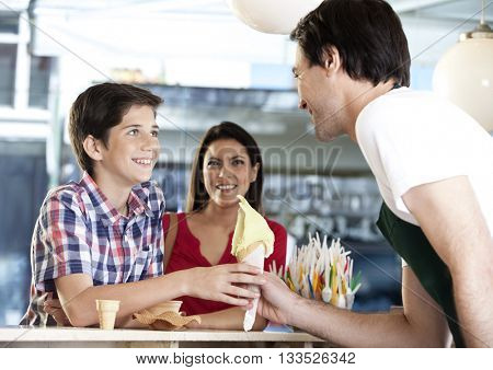 Boy Receiving Vanilla Ice Cream Cone From Waiter By Mother