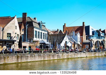 Bruges, Belgium - April 10, 2016: Panorama with canal and restaurants in traditional houses against blue sky in Brugge, Belguim