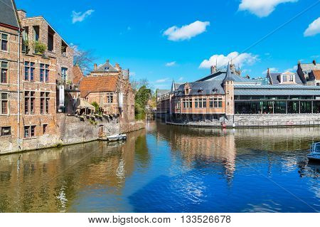 Ghent, Belgium - April 12, 2016: View of old colorful traditional houses along the canal in popular touristic destination Ghent, Belgium