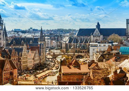 Ghent, Belgium - April 12, 2016: Aerial panoramic cityscape view of Ghent, Belgium with St. Michael Bridge, canal, traditional medieval houses, church against cloudy blue sky