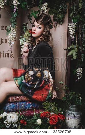 Magic portrait of romantic beautiful girl with wavy hair, red lips, art dress, holding rose flower, sitting on books.  Fashion fairy tale about princess, walking mistery forest. Creative concept