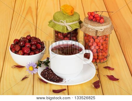 A cup of fruit tea, jars with berries of mountain ash and rosehip, bowl against the backdrop of pale wood.