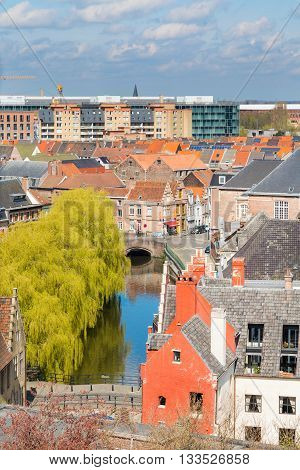 Ghent, Belgium - April 12, 2016: Aerial panoramic cityscape view of Ghent, Belgium with canal, traditional medieval houses against cloudy blue sky