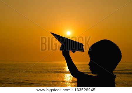 Silhouette boy playing with paper airplane and rising sun on beach
