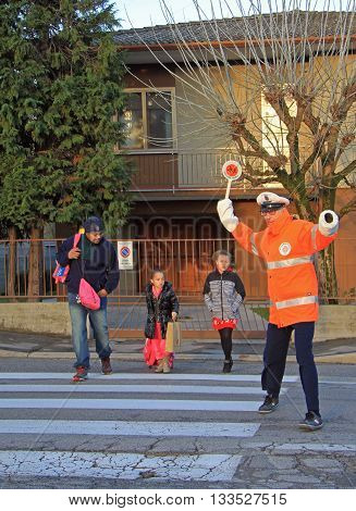 Vicenza Italy - November 24 2015: traffic controller is helping cross a pedestrian crossing in Vicenza Italy