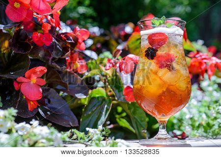 Glass of iced tea with raspberries and ice