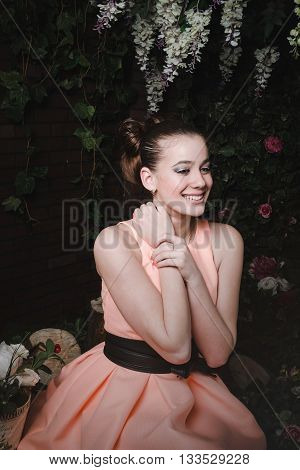 Smiling beautiful princess in beige evening dress with black belt, stylish hairstyle, make up. Fashion female in floral magic forest. Fashionable style female in scenery of Alice in Wonderland. Vintage young woman.