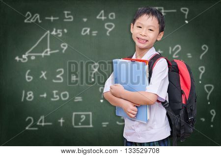 Asian schoolboy in uniform standing in front of chalkboard