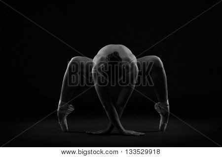 Art nude. Perfect flexible sexy body of young woman on black background. Studio shot