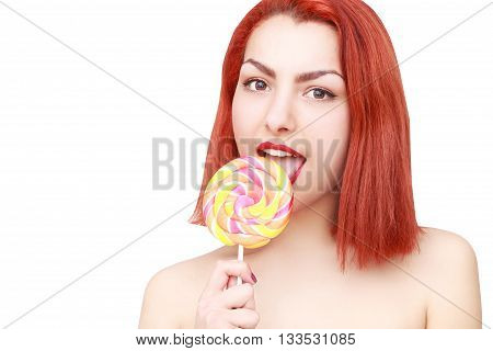 Lovely young woman fooling around, licking lolipop, isolated on white background