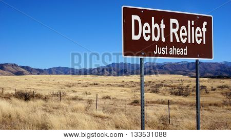 Debt Relief brown road sign with blue sky and wilderness