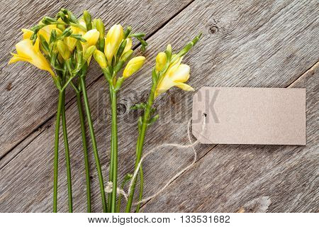 Yellow freesia flowers with blank tag on old wooden background