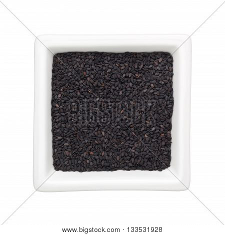 Black sesame seeds in a square bowl isolated on white background