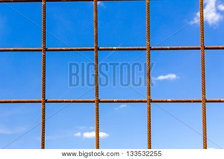 Rusty concrete reinforcement steel bars with blue sky in background.