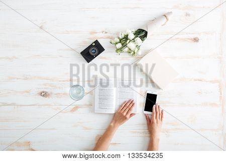 Women hands turn over book pages and holding smartphone on the wooden desk