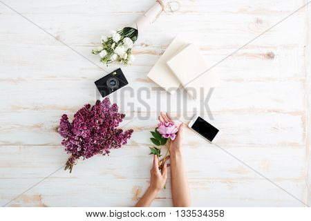 Women hands with peony flower, books, camera, glass of water and lilac bouquet on the wooden desk