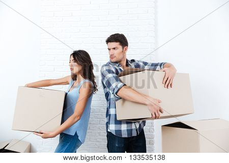 Young married couple is arguing during unpacking in a new house