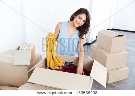 Portrait of a pretty young cheerful girl unpacking in new flat
