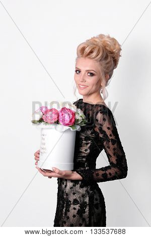 Beautiful lady in elegant black evening dress with updo hairstyle and flowers in a box in her hands. Fashion photo