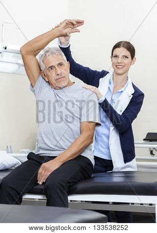 Physiotherapist Assisting Senior Male Patient To Exercise