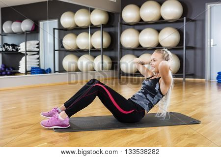 Woman Performing Crunches On Exercise Mat In Gym