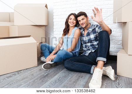 Young married couple with boxes and flat keys