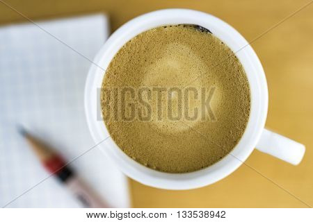 High Angle Still Life View of Cup of Frothy Coffee Resting on Wooden Table or Desk with Sharpened Pencil and Pad of Grid Paper Diffuse and Out of Focus in Background