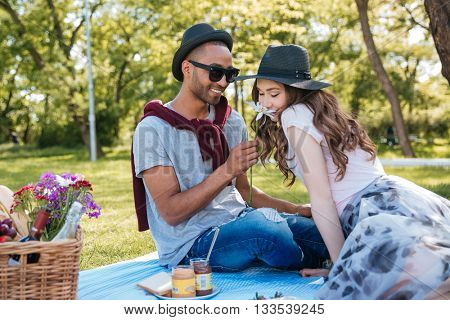 Beautiful young couple smelling flowers and having a picnic in park