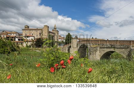 Roman Bridge people river houses and Church of Monastero Bormida in Piedmont Italy