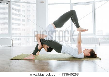 Two pretty young women doing acro yoga in studio together